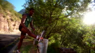 African American runner massaging his muscles during outdoor exercise video