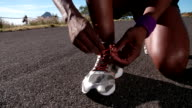 African American runner tying his laces, close up slow motion video