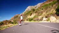 African American teen girl on a longboard doing downhill racing video