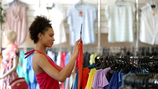 African american woman chooses clothes in shop video