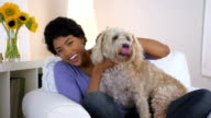 African American woman posing with dog in lap video
