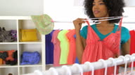 African American woman trying on pink dress and smiling video