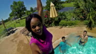 African American young woman smiles while diving into backyard swimming pool video