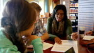 African American young woman tutor or teacher helps group of students in library video