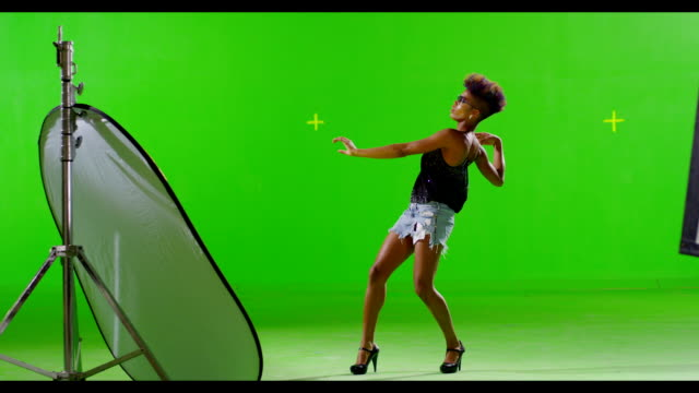 African black stylish girl dancing on green screen. Slow motion. video