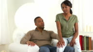 African couple sitting in living room video