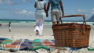 African couple walking on the beach, holding hands video