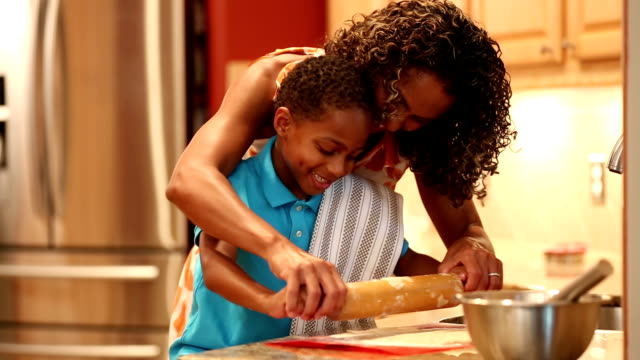 African descent mother teaches son how to make cookie dough. video