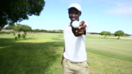 African golfer showing his golf ball to the camera video