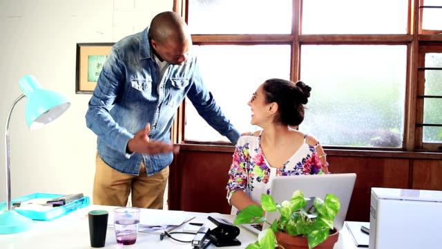 African man and female Hispanic colleague creative studio office video
