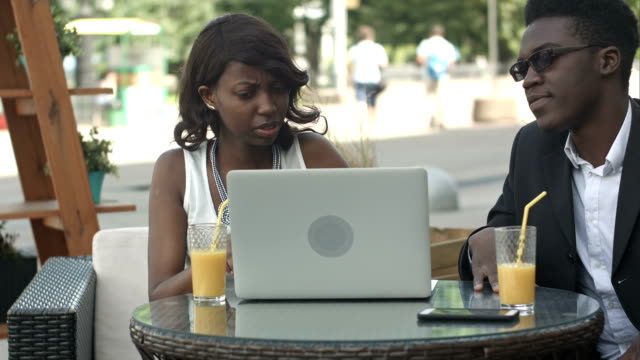 African man in formal suit explaining business strategy to his African female colleague using laptop during meeting, giving high five at a cafe video