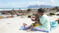 African mother and son at the beach, putting sunblock on video