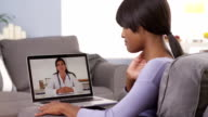 African woman talking with doctor online video