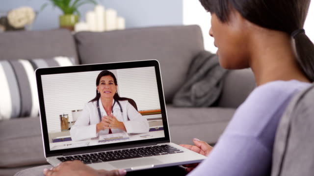 African woman webchatting with doctor video