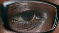 ECU African-American brown eye looking through glasses video