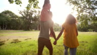 African-american family walking together in beautiful green park video