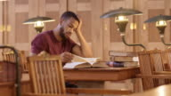 LD African-American male student studying in the library video