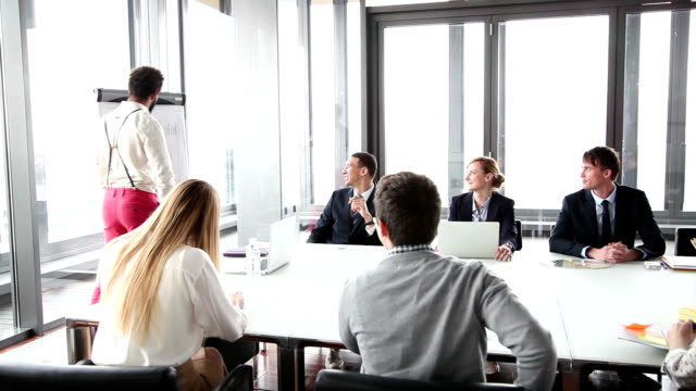 African-american man giving presentation while colleagues sitting at table video