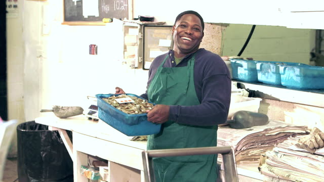 African-American man working in fish market video