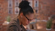 African-American woman with glasses working behind office desk video