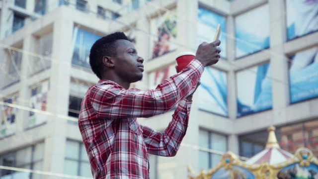 Afro american young man taking photo of skyscrapers video