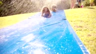 Afro girl and friends playing on a water slide video