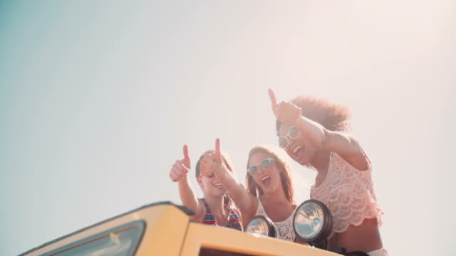 Afro girl and friends thumbs up on road trip video