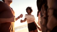 Afro girl dancing with her boyfriend at a sunset beachparty video