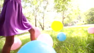 Afro girl happily playing with colourful balloons in a park video