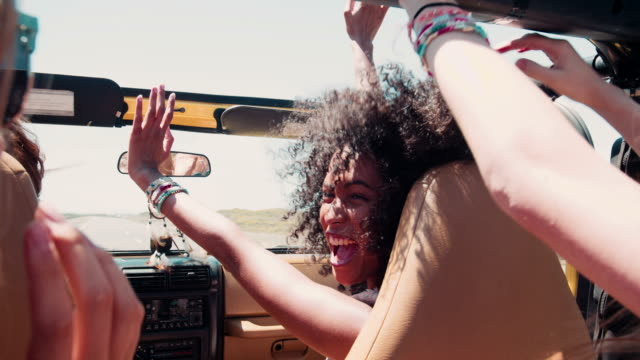 Afro girl laughing with friends on a road trip vacation video