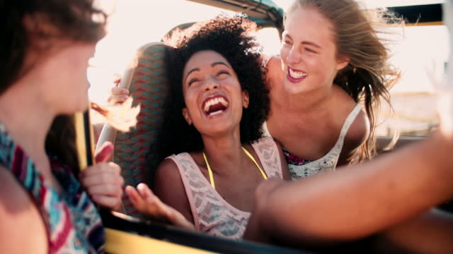 Afro girl laughing with friends on road trip slow motion video