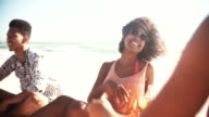 Afro girl relaxing at the beach with friends video