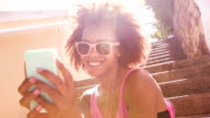 Afro haired girl texting on smartphone video