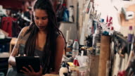 Afro woman in leather apron using digital tablet in workshop video