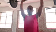 Afro-American boy training with barbell weights at the gym video