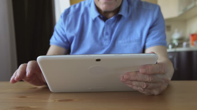 Aged male hands types on a white tablet PC on a table - front view video