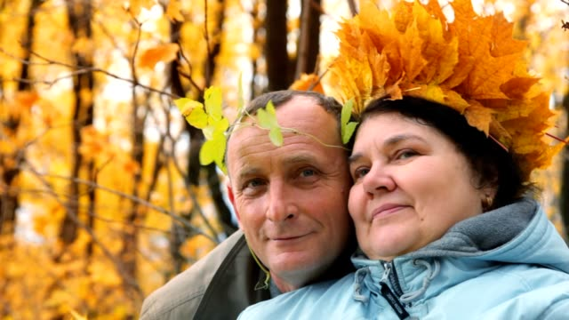 Aged man and woman standing in autumn park video