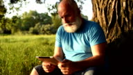Aged man is sitting beneath a tree with his data tablet video