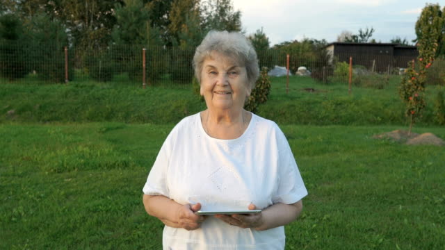 Aged woman 80s holding computer tablet outdoors video
