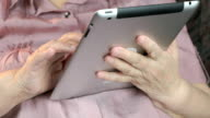 Aged woman 80s holds the silver tablet computer video