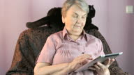 Aged woman sits at a armchair next to a black cat video