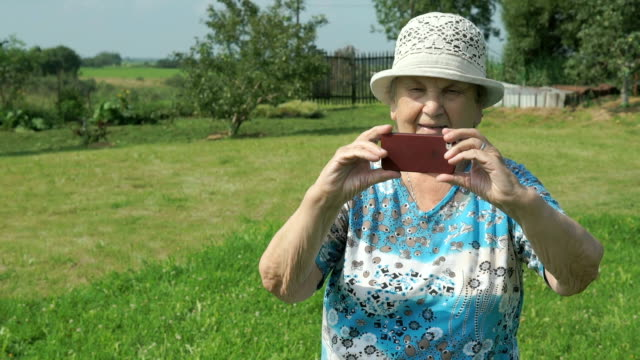 Aged woman taking photos the nature of park video