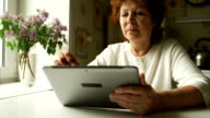 Aged woman using a digital tablet PC at home video
