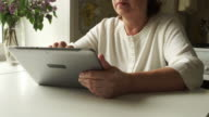TRACKING: Aged woman using a digital tablet PC at home video