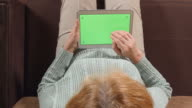 TOP VIEW: Aged woman with a tablet PC (green screen) on a sofa  - close up video