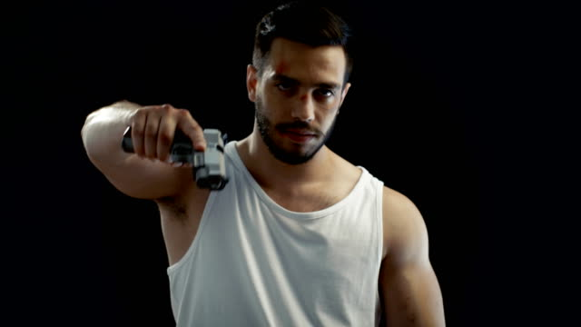 Aggressive Man with a Bruised Face Wearing Singlet, Aims His Gun into Camera and Threatens with it. Background is Isolated Black, video