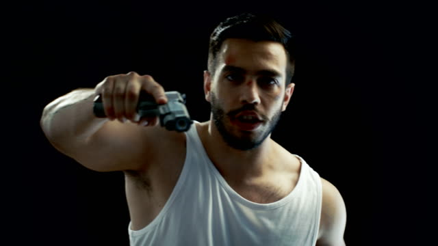 Aggressive Man with a Bruised Face Wearing Singlet, Waves a Gun and Threatens with it. He Looks like a Gang Member. Background is Isolated Black, video