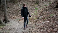 Aggressive young man walking alone in forest, annoyed with life, video