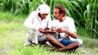 Agronomist consulting with farmer using digital tablet video