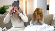 Ailing Pair With Runny Nose Using Nasal And Throat Spray Sitting In Living Room video